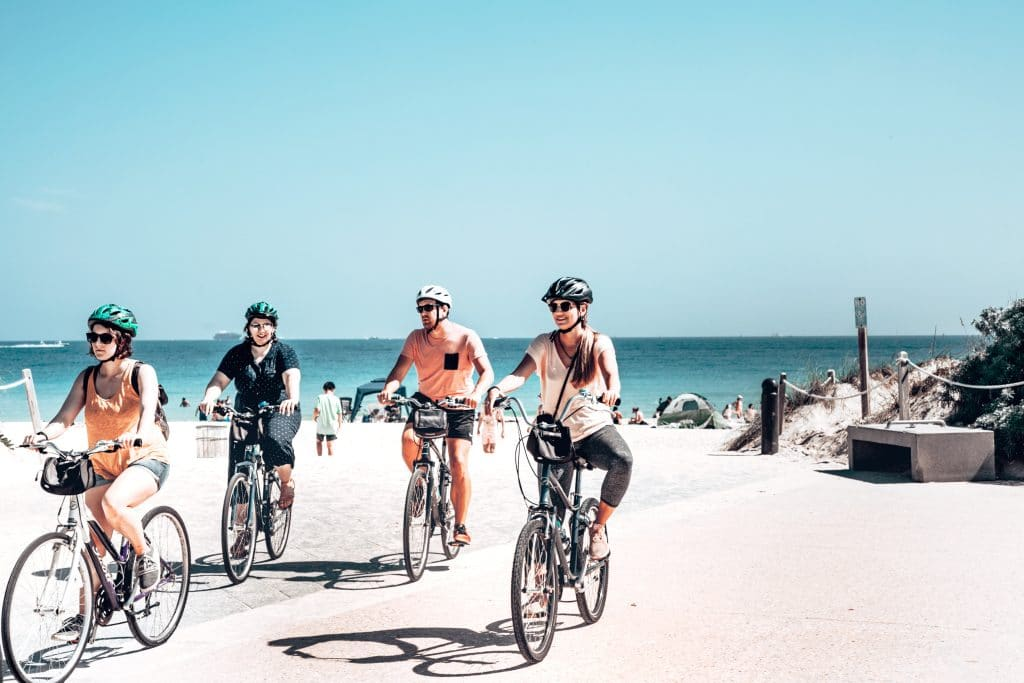 cyclists with helmets riding on the beach